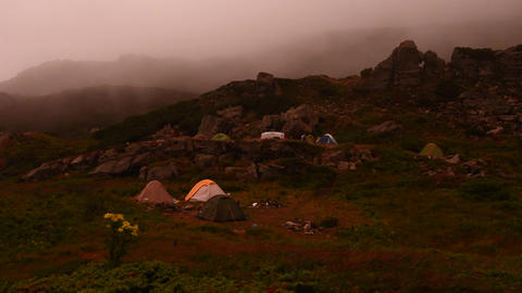 Tent camp in the mountains, camping by the lake, tents removed from the top Live Action
