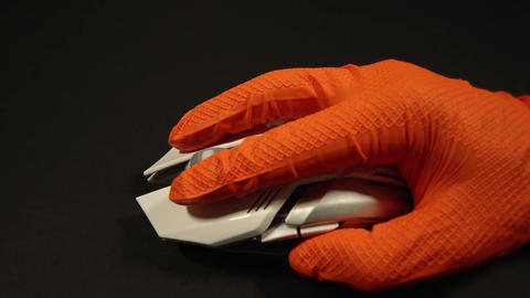 person in gloves uses wireless mouse on black background Live Action