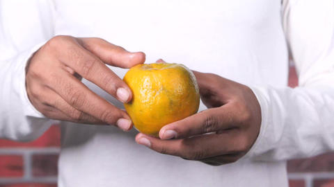 young man taking skin off from a orange fruit Live Action