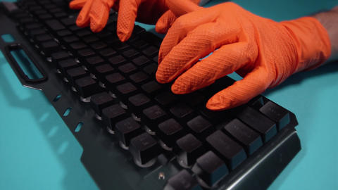 motion around person in gloves with keyboard at blue table Live Action