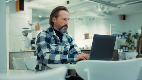 Adult senior man work remotely on laptop at cafe Live Action