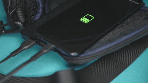 the phone is charged from a power bank lying on a backpack. Smartphone charging Live Action