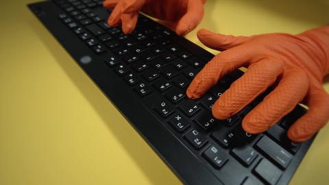 motion around person in gloves typing on keyboard at table Live Action
