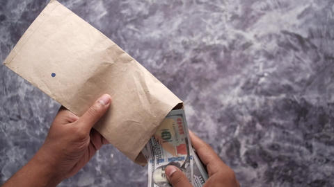person hand putting cash in a envelope Live Action