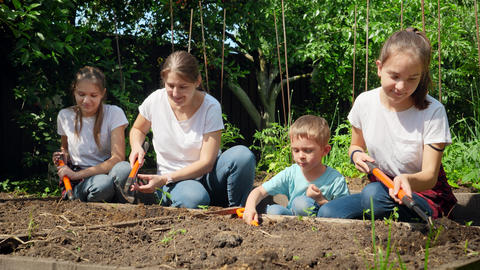 Children helping mother working in garden and planting vegetables on garden bed Live Action