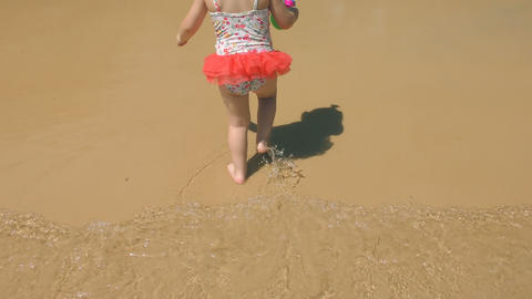 Little girl in swimsuit running on the beach Footage