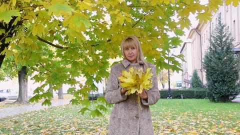 Beautiful woman with yellow leaves near a beautiful tree rejoices at the Live Action