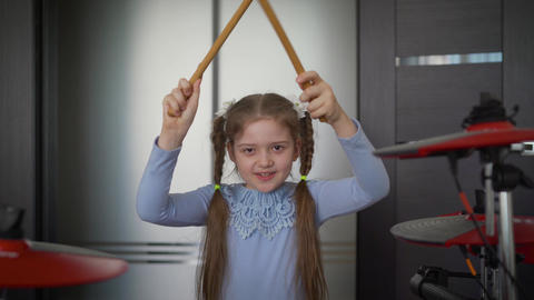 A little girl plays electronic drums at home. Cheerful girl with drum sticks Live Action