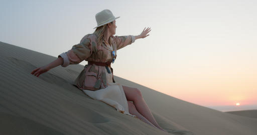 Cheerful girl sitting on sand dunes in dessert Live Action