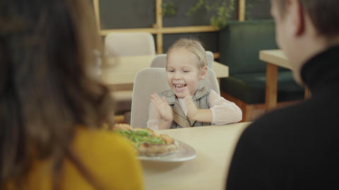 Cheerful charming little girl clapping as waiter bringing pizza in restaurant Live Action