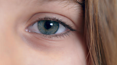 Girl's eye close up of blue color looking at the camera. Concept of childhood Live Action
