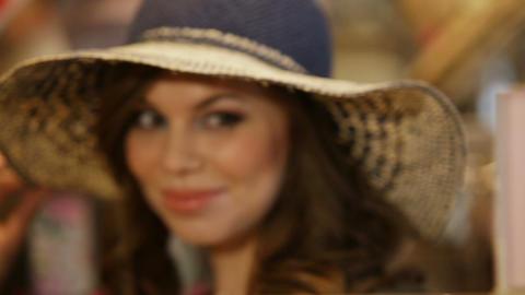 Cheerful woman tries on elegant summer straw hat near mirror Live Action
