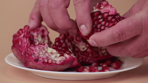 With a slow movement, male hands take out pomegranate seeds Live Action