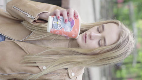Vertical video of a young skinny girl in the park. The girl is drinking coffee Live Action