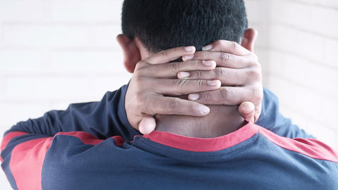 man suffering from neck pain at home Live Action