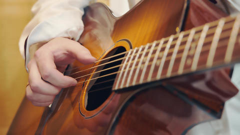 A male hand plays the guitar close up in warm light and warm tones. Playing Live Action