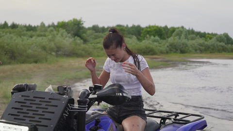 Girl and dirt after riding an ATV. The girl sits and shakes off the dirt. The Live Action