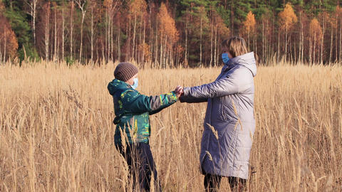Mom and son dance on the tall grass, rejoice at freedom, have fun Live Action