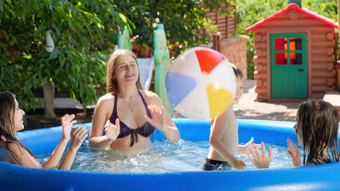 Cheerful bog family playing with beach ball in inflatable swimming pool in the Live Action