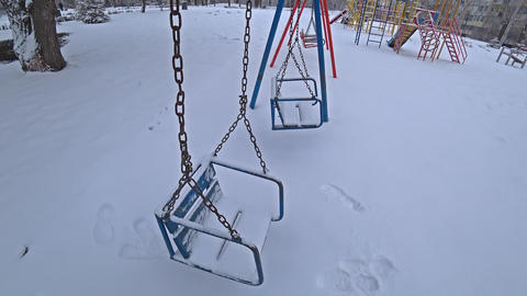 Empty children swings on a playground in city park at sunny winter day, wide angle, 4k Live Action