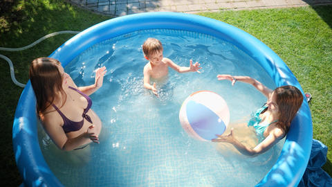 Slow motion of happy cheerful family having fun with inflatable beach ball in Live Action