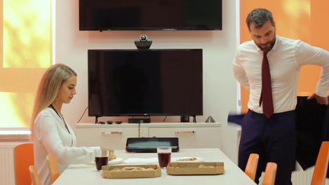 Colleagues have lunch break in corporate building eating space, eating pizza Live Action
