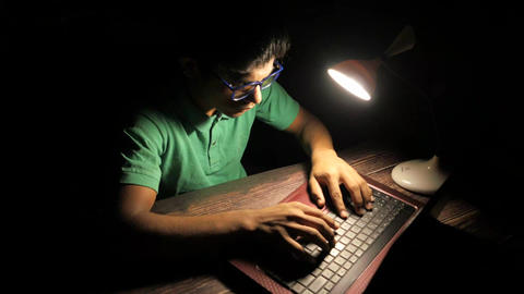 young man working on laptop stealing personal data Live Action