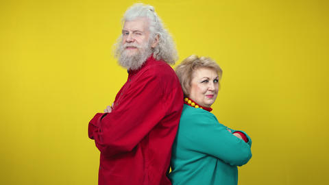 Confident senior man and woman standing back to back on yellow background Live Action