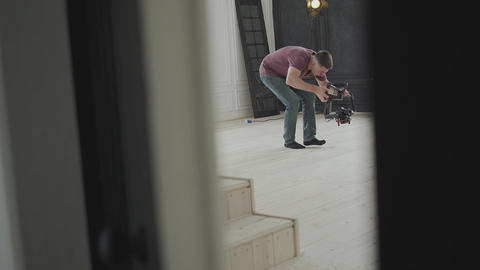 The videographer shoots using an electronic stabilizer.Camera Gimbal DSLR Video Live Action