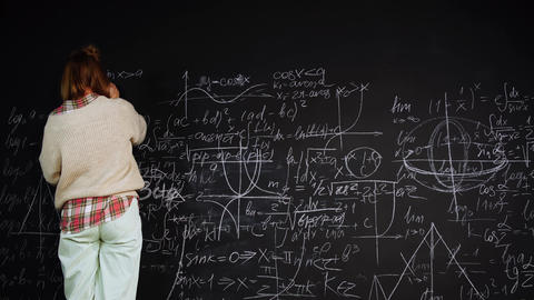 Woman solves scientific problem writing formulas on chalkboard focused on Live Action