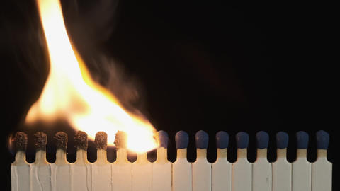 Alternately lighting a match in a row of matches. Matches lit in row burning in Live Action