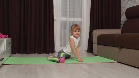 Girl kid girl doing gymnastics stretching workout at home, watching online Live Action