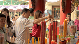 Thai People Lighting Candles at a Temple Stock Video Footage