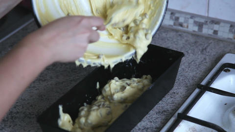 Moving cake pastry with raisins from bowl to baking dish, timelapse Footage