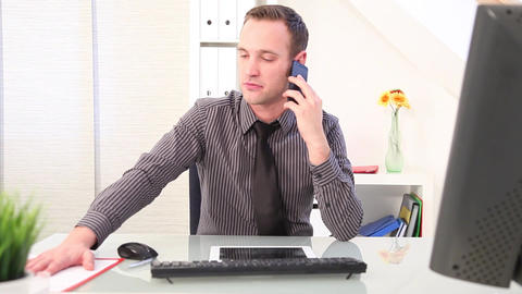 Businessman Typing On A Keyboard And Talking On Phone stock footage