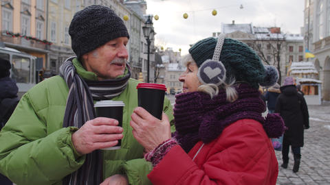 Senior wife husband tourists drinking from cups, enjoying hot drink tea on city Live Action
