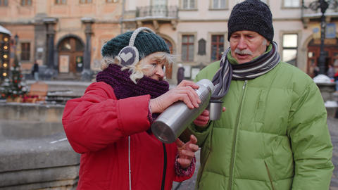 Senior wife husband tourists drinking from thermos, enjoying hot drink tea on Live Action