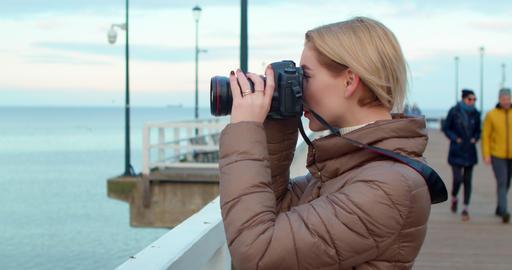 Beautiful female photographer photographs the ocean Animation