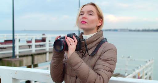 Creative young female photographer takes pictures with a professional camera Animation