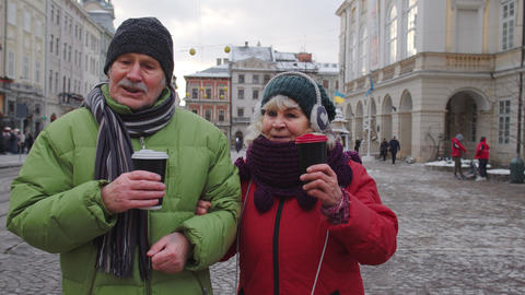 Senior old tourists grandmother grandfather walking, drinking hot drink mulled Live Action