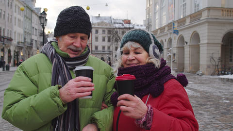 Senior tourists grandmother grandfather traveling, drinking hot drink mulled Live Action