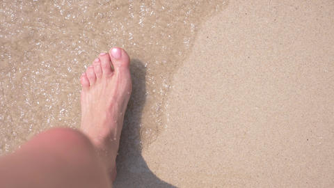 female feet on the sand, the sea wave covers the female legs. 4k, slow motion Live Action