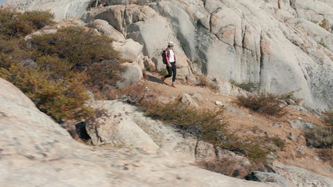 Young Woman Hiking mountains on Summer or Spring. Active traveler with backpack Live Action