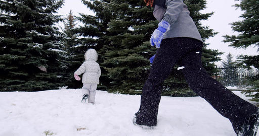 Slow motion. Cheerful children play snowballs on the street, run and throw Live Action
