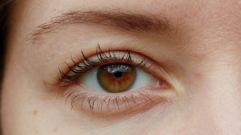 Close-up of brown eye. Young Woman is opening and closing her beautiful eye Live Action