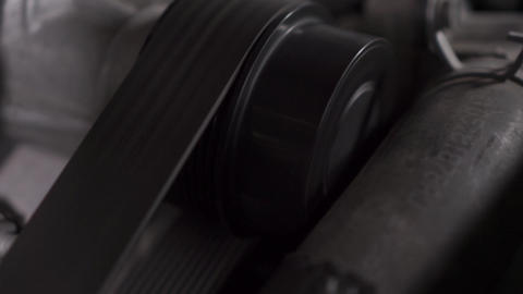 Closeup shot of rotating belts on car engine. Footage. Extreme close-up video Live Action