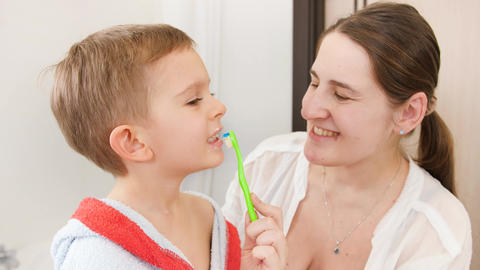 Portrait of little smiling boy brushing and cleaning teeth with his smiling Live Action