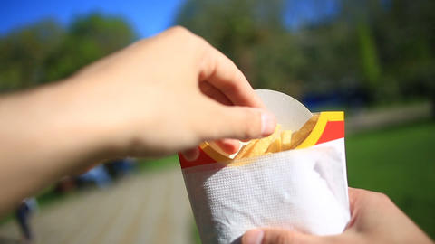 A man eats fast food on the street. He carries a French fries and eats it Live Action