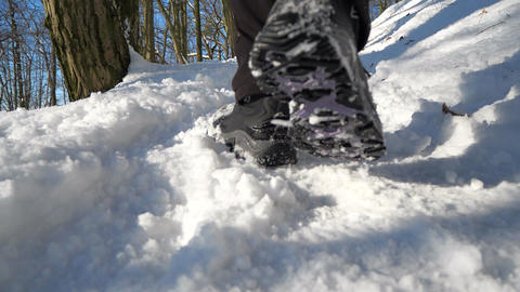 Leg teenager in winter shoes walking on the snow in a winter park. Sunny winter day Live Action