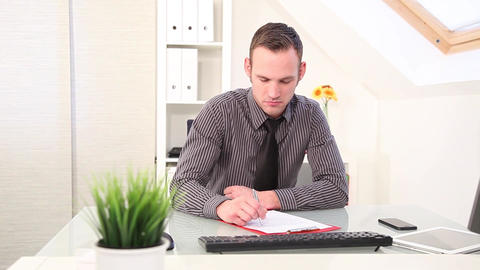 Businessman writing notes at his desk Stock Video Footage